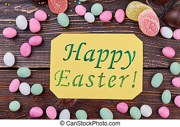 Happy Easter card with sweets. Colorful candies on dark...