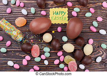 Happy Easter card, scattered sweets. Candies on dark brown...