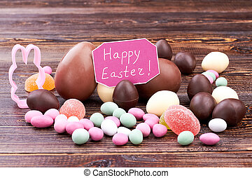 Happy Easter card and candies. Different sweets on brown...