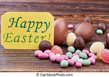 Happy Easter card, colorful sweets. Candies on wooden...