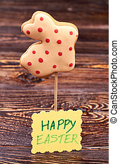 Cookie and Happy Easter card. Rabbit shaped biscuit on...