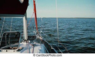 Sailboat moving in the lake, splashing water. Yacht breaking...