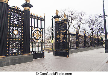 Beautiful pig-iron gate open an entrance to the park