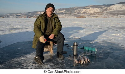 Fisherman is a man in winter fishing.