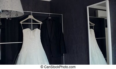Wedding day. Dress and suit hanging in the apartment....