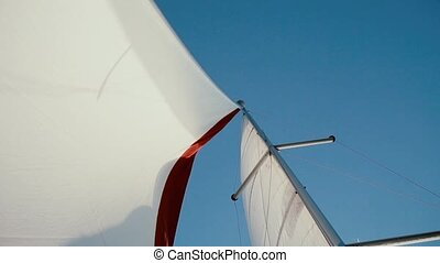 Close-up view of white and red sail waving in the wind in...