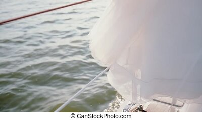 Close-up view of board of the sailboard. White dress hangs on the yacht. Ship goes through the waves with full speed.