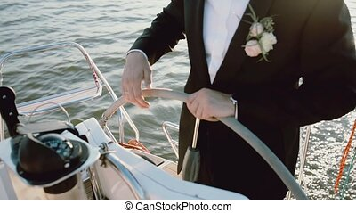 Close-up view of the groom in a wedding suit standing behind...
