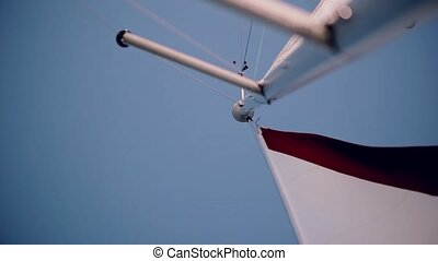 White and red sail waving in the wind in bright summer day....