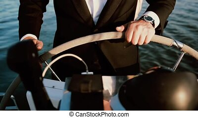 Businessman standing behind a steering wheel on the ship. Young sailor driving the sailboard in sunny day. Close-up view