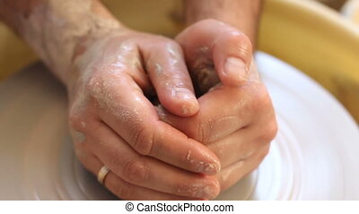 close up of man hands teaching to work with claim in pottery