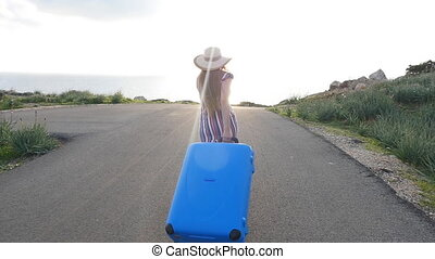 Young woman traveler in a hat runs with a blue suitcase
