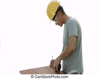 Measuring - Construction worker measuring a board before...
