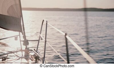 Close-up view of nasal part of the yacht moving in the sea. Sailboat going through the water in bright sunny day.