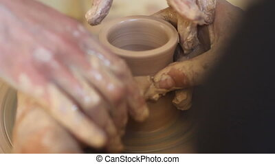 potter teaching how to made a craft cup. close up -...