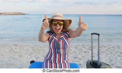 Happy young woman sitting on a suitcase showing thumbs up....