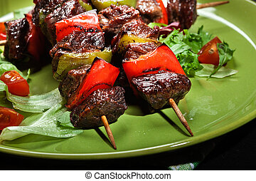 Grilled beef meat and vegetable kebabs on the green plate