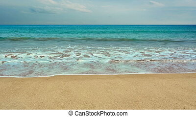 Wild tropical sandy beach with waves.