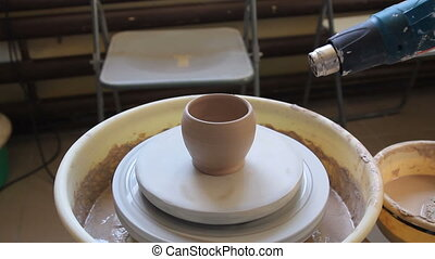 Potter dries a cup with a construction hair dryer - Potter...