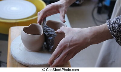 Close up of a man's hands making a clay cups in shape of...