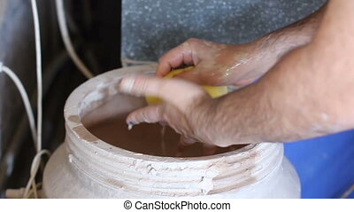 Potter washes his hands in a barrel after work - Potter...