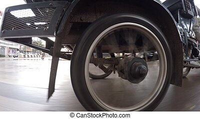 Wheel of motorcycle rickshaw close up. Movement on a rainy...