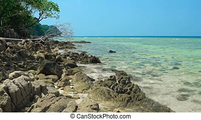 Warm Sea Water Washes over a Rocky Tropical Beach - Warm sea...