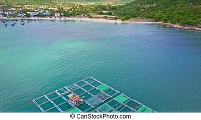 Aerial View Motion Over Lobster Farm along Ocean with Boats...