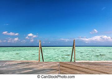 Wooden jetty towards water villas in Maldives. - Wooden...