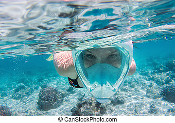 Woman snorkeling underwater in Indian Ocean, Maldives. Clear...