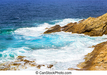Waves break on rocky shore. Bali, Crete - Waves break on...