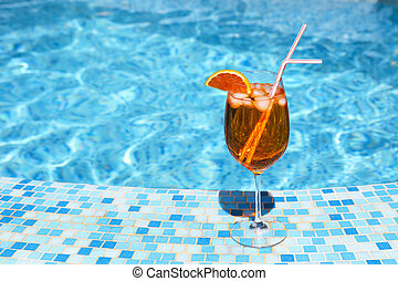Glass of alcohol cocktail near the pool - Glass of orange...