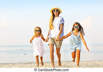 Happy young family having fun running on beach at sunset....