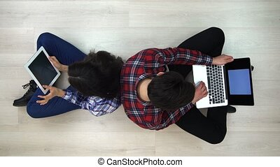 Top view of man and woman working back to back