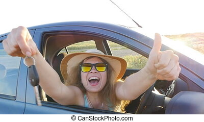 Young woman showing key to new car - Young woman showing key...