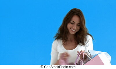 Glad woman opening shopping bags standing against a blue...