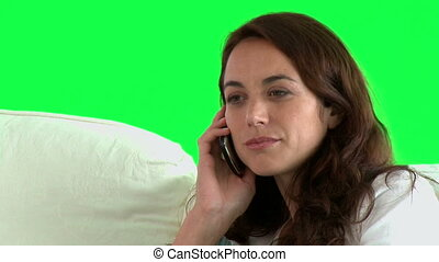 Hispanic woman on phone sitting on a couch against a green...