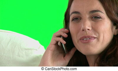 Portrait of a woman on phone sitting on sofa against a green...