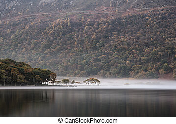Stunning Winter foggy sunrise on Crummock Water in Lake District England