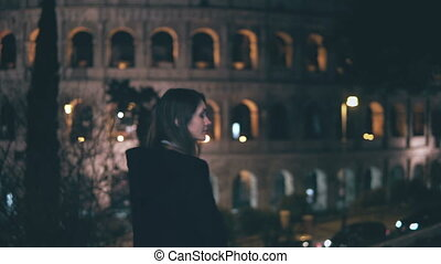 Portrait of young brunette woman standing near Colosseum in Rome, Italy in evening. Girl turns and looks at camera.