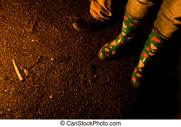 Boots of People Around Bonfire - View of the feet of people...