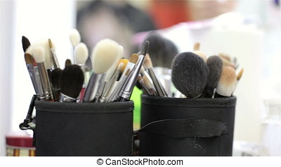 Make-up brushes and products on table