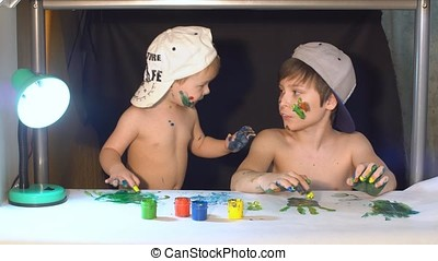 Two brothers draw fingers on paper. Their hands smeared with paint