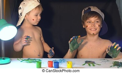 Two brothers draw color paints on the face. Family concept.
