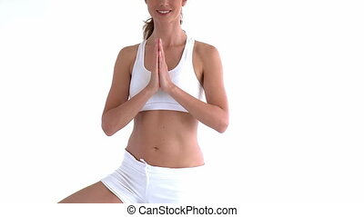 Close up of a woman doing yoga pose standing against a white...