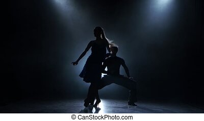 Professional couple of rumba dancers posing in smoky studio, silhouette