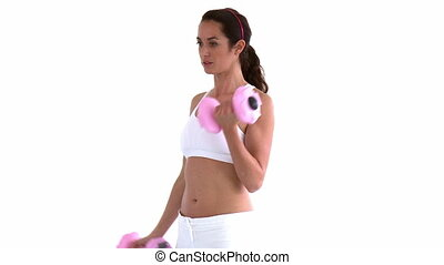 Hispanic woman training with dumbbells against white...