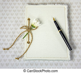 daisy and fountain pen on diary - close journal with white...