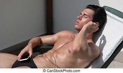 Shirtless muscular young man sunbathing, listening to music...