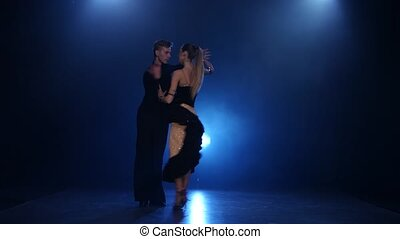 Rumba dancing pair of professional elegant dancers in smoky...